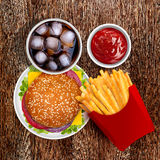 Cheeseburger with french fries and cold cola. Delicious Cheeseburger with fresh tomato, lettuce and onion, with golden french fries and cold cola Stock Images
