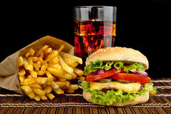 Cheeseburger with french fries with glass of cola on wooden mat on black Stock Photography