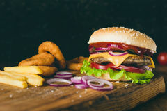 Cheeseburger, french fries and onion rings. Fast food. Cheeseburger, french fries and onion rings on wooden cutting board over wooden background. Closeup view Royalty Free Stock Images