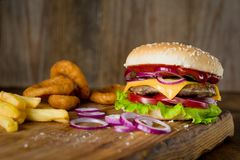 Cheeseburger, french fries and onion rings on wooden chopping board over wooden backdrop. Horizontal, closeup view Royalty Free Stock Photo