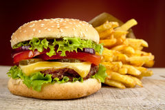 Cheeseburger and french fries on red spotlight on wooden table Stock Image