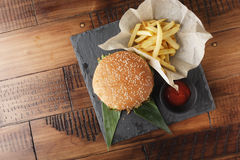 Cheeseburger with french fries. And sauce on a brown wooden background Stock Photography
