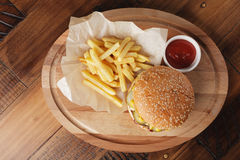 Cheeseburger with french fries. And sauce. Hamburger on a brown wooden background Stock Photo