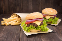 Cheeseburger with french fries on wooden background Royalty Free Stock Images