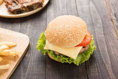 Cheeseburger and french fries on the wooden background Royalty Free Stock Photo