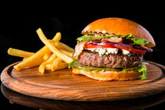 Cheeseburger with french fries on a wooden board Royalty Free Stock Photos