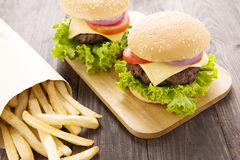 Cheeseburger with french fries on wooden table Royalty Free Stock Photography