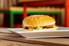 Cheeseburger fresco del primer en la placa blanca en el blurre de madera de la tabla Fotografía de archivo