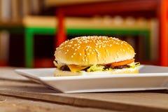 Cheeseburger fresco del primo piano sul piatto bianco al blurre di legno della tavola Fotografia Stock