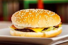 Cheeseburger fresco del primo piano sul piatto bianco a fondo vago Immagine Stock Libera da Diritti