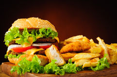 Cheeseburger, fried chicken nuggets and french fries stock photos