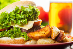 Cheeseburger with fried potatoes on a plate with beer Royalty Free Stock Photos