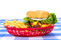 Cheeseburger and fries. A freshly grilled cheeseburger in a red basket with freshly cooked french fries royalty free stock photos