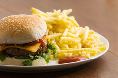 Cheeseburger with fries. Bacon cheeseburger with fries on tabletop Royalty Free Stock Photos