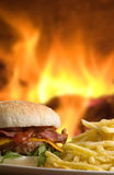 Cheeseburger with fries. With fire as background Royalty Free Stock Photography