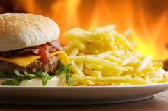 Cheeseburger with fries. With fire as background Stock Photo