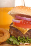Cheeseburger fries and beer. Freshly grilled cheeseburger with onion rings and beer royalty free stock image