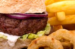 Cheeseburger, Fries and Onion Rings. Quarter Pound Cheeseburger, a tower of fries and battered onion rings presented on a slate platter Stock Photo