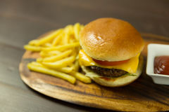 Cheeseburger, fries and red ketchup sauce. Tasty burger with all the trimmings Stock Image