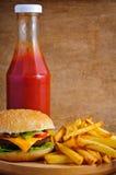 Cheeseburger, fritadas y salsa de tomate Foto de archivo libre de regalías