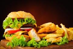 Cheeseburger, gebraden kippengoudklompjes en frieten Stock Foto's