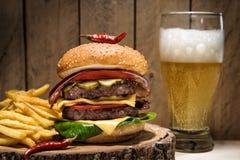 Cheeseburger grande com pimenta de pimentão, batatas fritas e um vidro da cerveja no fundo de madeira fotos de stock royalty free