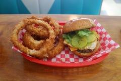 Cheeseburger grillé délicieux et anneaux d'oignon frits photos libres de droits