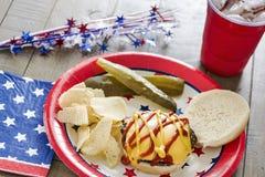 Cheeseburger with ketchup and mustard at a patriotic themed cookout. A cheeseburger with ketchup and mustard at a patriotic themed BBQ.  It is served with potato Royalty Free Stock Image