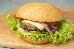Cheeseburger with lettuce, tomato, and onion on a brioche bun.  stock photo