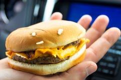 Cheeseburger. Man holding a fast food cheeseburger with bacon Royalty Free Stock Photos