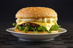 Cheeseburger with mayonnaise. Lettuce and onion on dish with black background Stock Photography