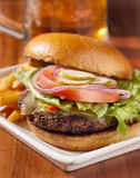 Cheeseburger meal. Gourmet cheeseburger with mug of beer in background stock image