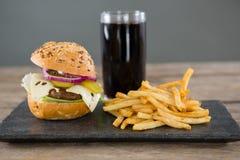Cheeseburger met frieten en drank op lei Stock Afbeeldingen