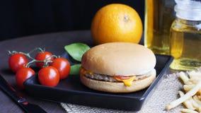 Cheeseburger mit den redtomatoes, orange im schwarzen Teller lizenzfreie stockbilder