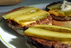 Cheeseburger mit Essiggurke Lizenzfreies Stockfoto