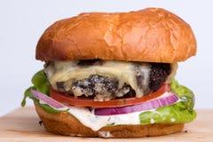 Cheeseburger mit Tomate, Zwiebel, Kopfsalat, mayonaisse auf hölzernem b Lizenzfreie Stockfotos