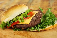 Cheeseburger mit Tomatenzwiebel und -kopfsalat stockbilder