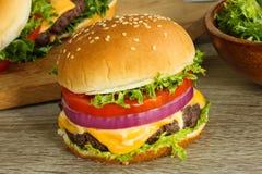 Cheeseburger mit Tomatenzwiebel und -kopfsalat Lizenzfreie Stockbilder