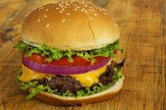 Cheeseburger mit Tomatenzwiebel und -kopfsalat Lizenzfreie Stockfotografie