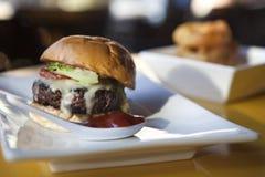 Cheeseburger mit Zwiebelen-Ringen Stockfoto