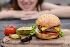 Cheeseburger na tabela de madeira, cara de sorriso Foto de Stock