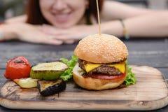 Cheeseburger na tabela de madeira, cara de sorriso Imagens de Stock