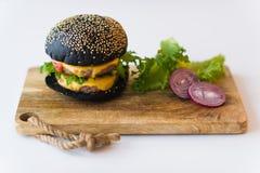 Cheeseburger negro en la tajadera de madera, fondo gris fotografía de archivo