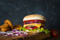 Cheeseburger and onion fries on wooden chopping board. Cheeseburger and onion rings on wooden cutting board over dark background. Closeup view, selective focus Stock Image