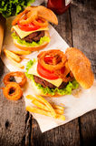 Cheeseburger and onion rings. Beef cheesburger with deep fried onion rings and french fries.Selective focus on the cheesburger Stock Photo