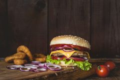 Cheeseburger and onion rings on wooden cutting board over wooden background. Closeup view with copy space for text Stock Images
