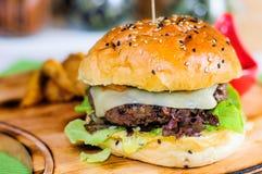 Cheeseburger op houten blok dichte omhooggaand stock fotografie