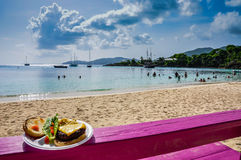 Cheeseburger in Paradise. Plate of cheeseburger and salad set on fuschia pink bench on Caribbean beach Stock Image