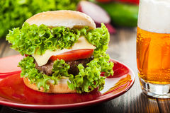 Cheeseburger on a plate with beer Royalty Free Stock Photos