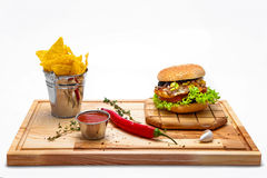 Cheeseburger with potato chips on a wooden board Stock Image
